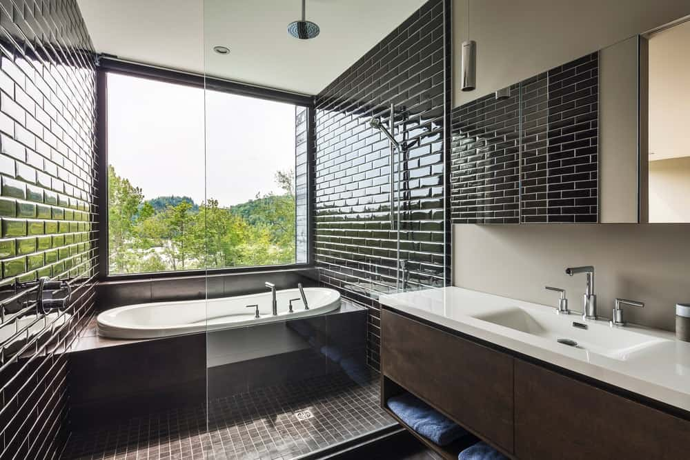 Master bathroom featuring elegant black tiles walls and a drop-in tub together with a single sink.