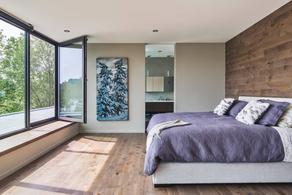 Contemporary primary bedroom with matching wooden planked wall and floor. It is designed with a pine tree canvas art piece mounted on a gray wall that opens to the primary bathroom.