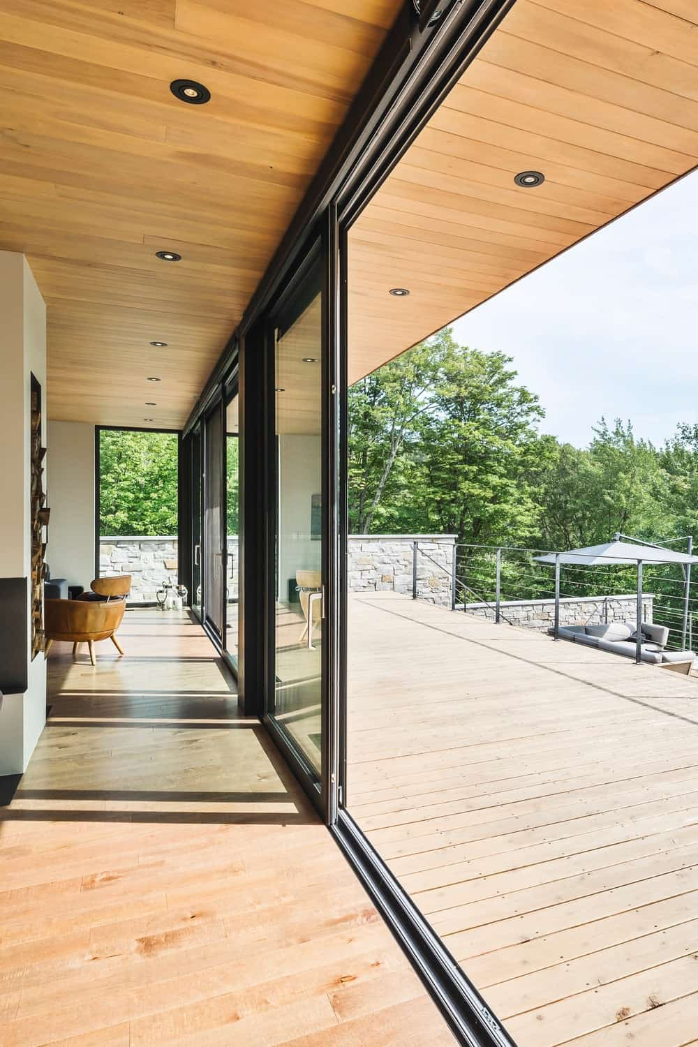 The house features a deck leading to the patio. Photo Credit: Ulysse Lemerise Bouchard