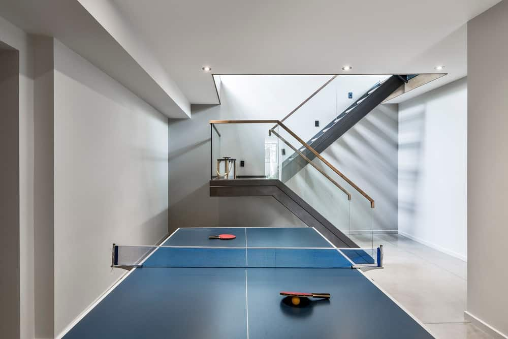 Game room with white walls together with a table tennis. Photo Credit: Ulysse Lemerise Bouchard