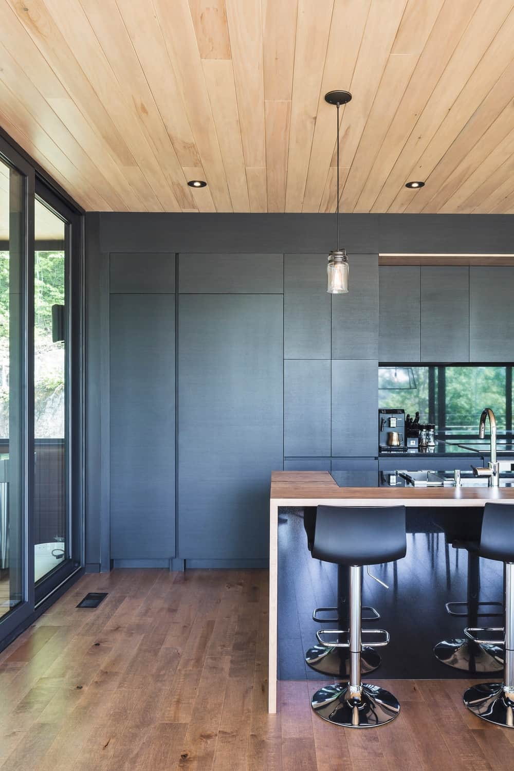 Kitchen with hardwood flooring and black walls together with recessed and pendant lights. Photo Credit: Ulysse Lemerise Bouchard