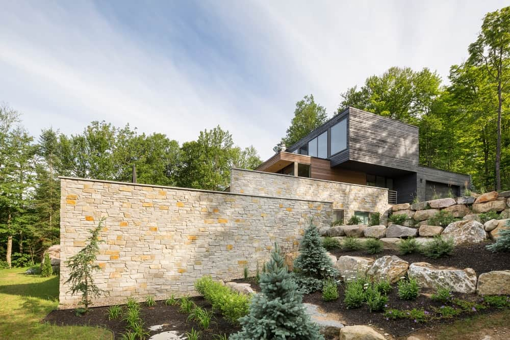 This side of the house boasts a steep bank landscaping planted with shrubs and layered with natural rocks complementing the stone walls.