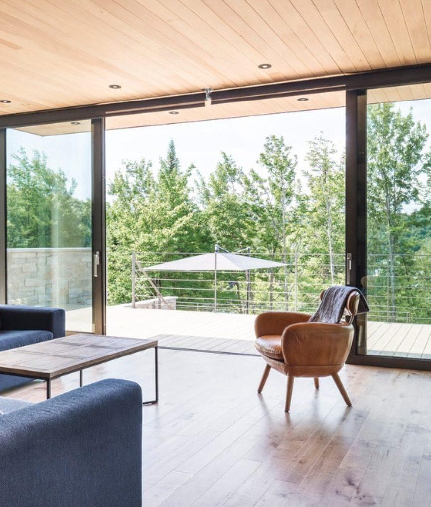 Living room with hardwood flooring and recessed lights. Photo Credit: Ulysse Lemerise Bouchard