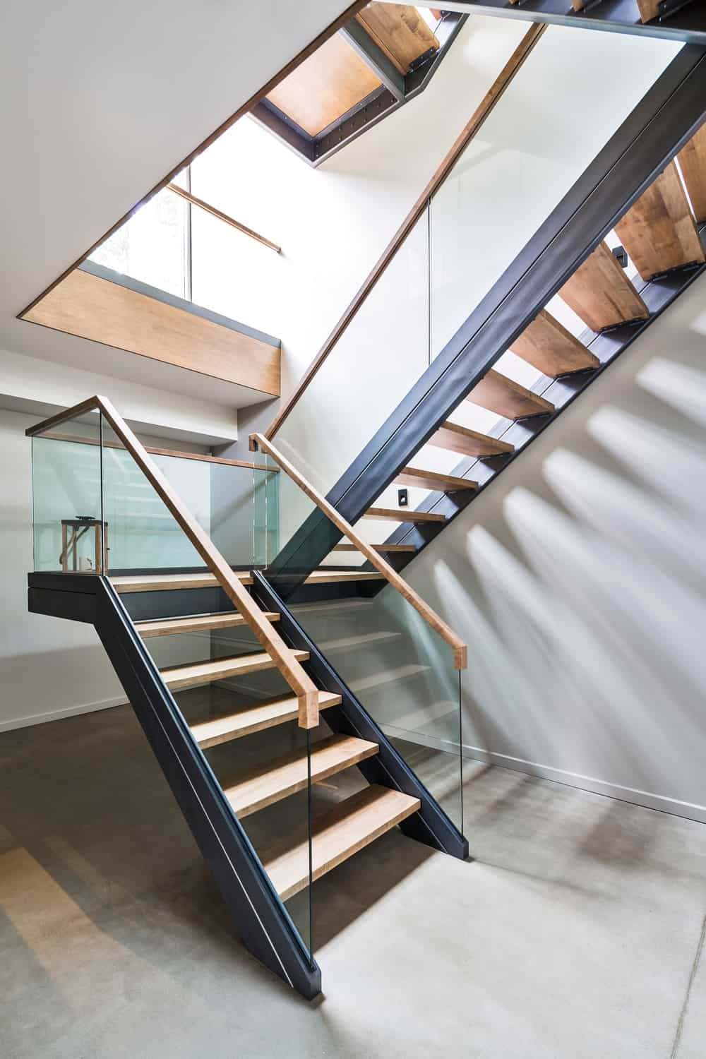 Staircase with hardwood floors and handrails. Photo Credit: Ulysse Lemerise Bouchard