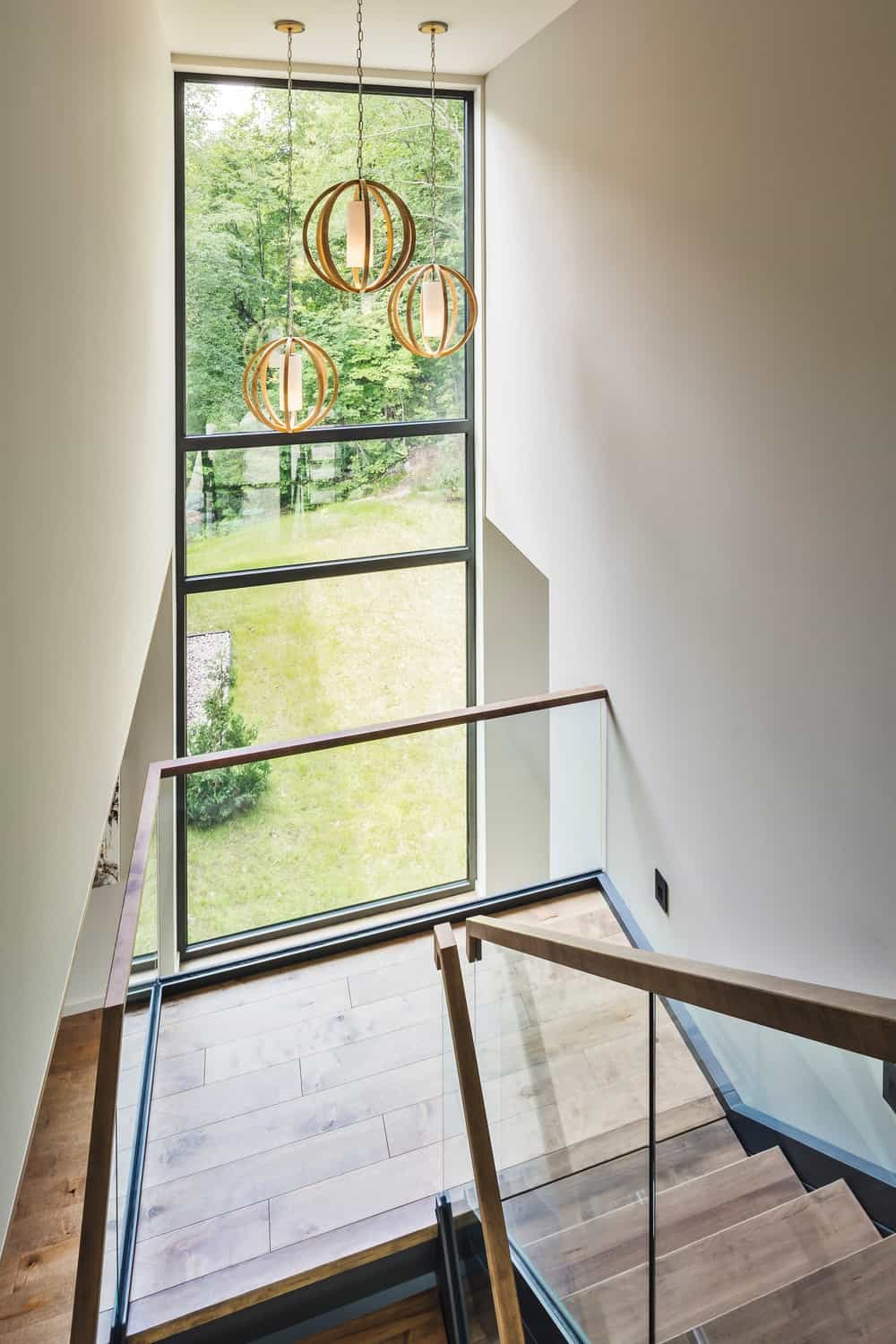 Staircase with hardwood floors and white walls together with pendant lights and glass window. Photo Credit: Ulysse Lemerise Bouchard