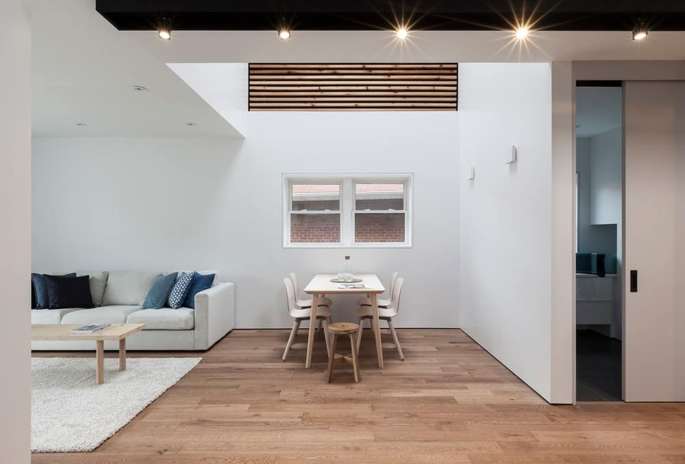 The small dining area features a small rectangular wooden table with matching chairs on a hardwood flooring.