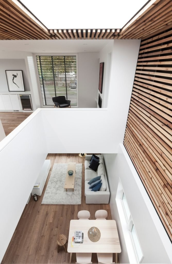 A view from above of this great room with a cozy living space and a square dining table set situated on the hardwood floors.