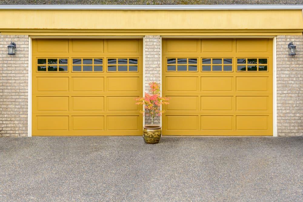 Garage door with small cluster windows in panel frames along top of garage door