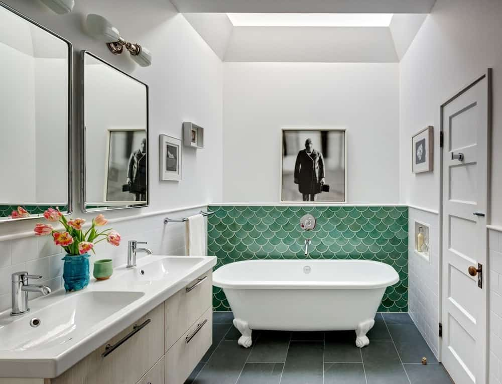 The primary bathroom boasts a freestanding tub with a shade of green wall. Double sink matches with white walls with a stylish wall art. Photo Credit: Francis Dzikowski/OTTO