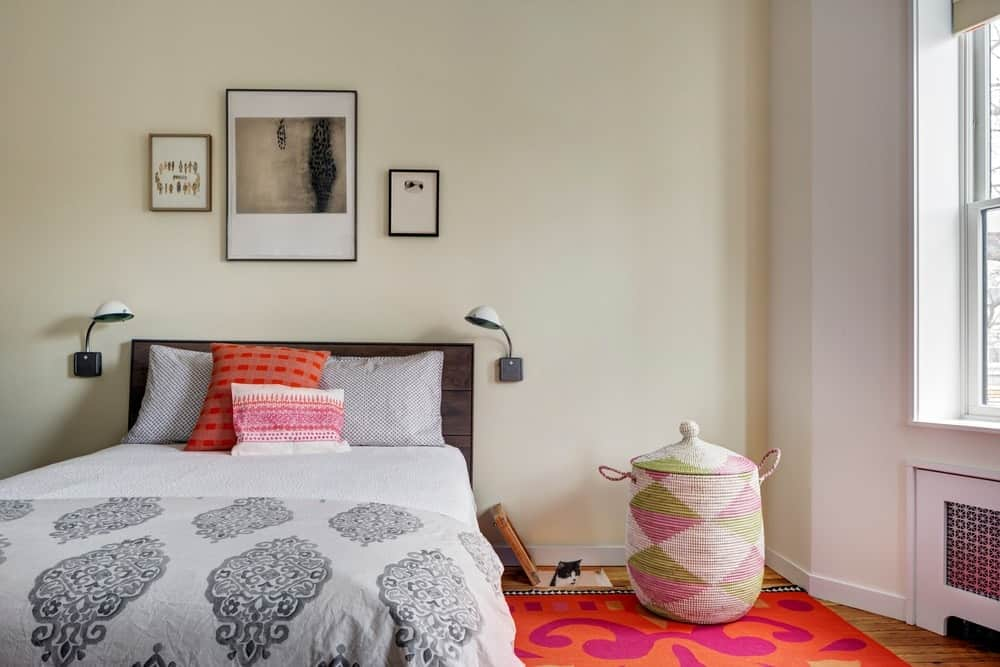 The bedroom has a nice wall walls surrounding it while the rug creates a colorful vibe. There's a cat area as well just beside the bed. Photo Credit: Francis Dzikowski/OTTO