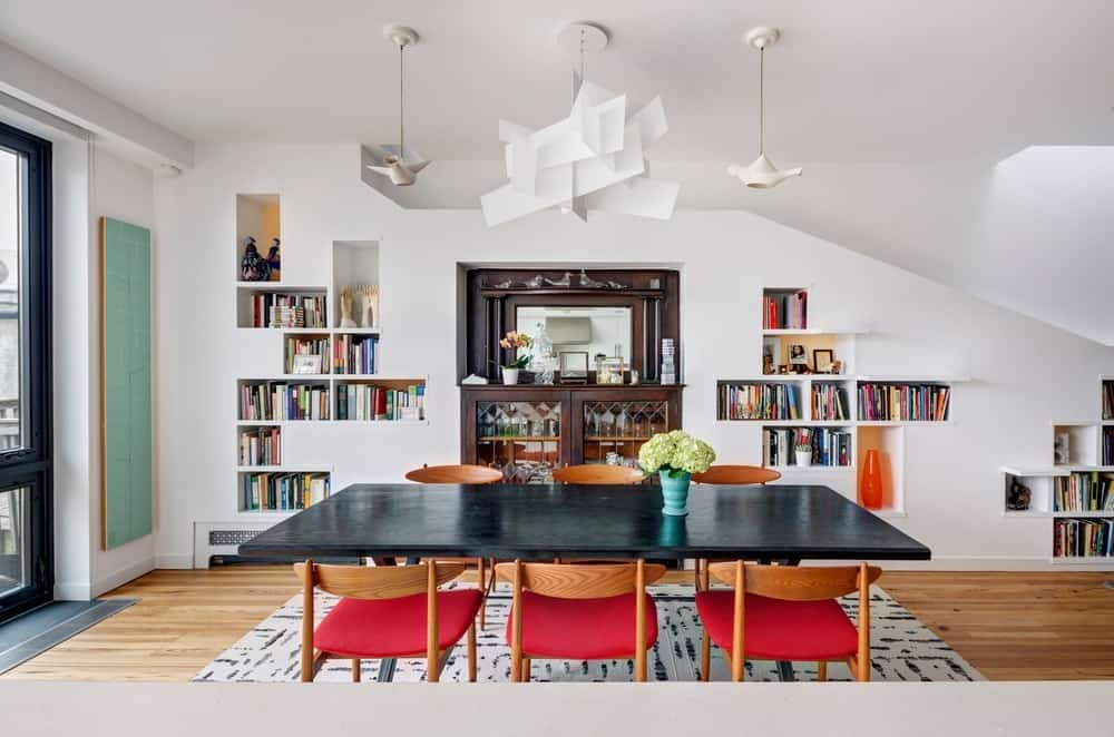 White dining area with interesting pendant lights that hung from the black dining table and red chairs. It includes built-in bookshelves with a display cabinet in the middle.