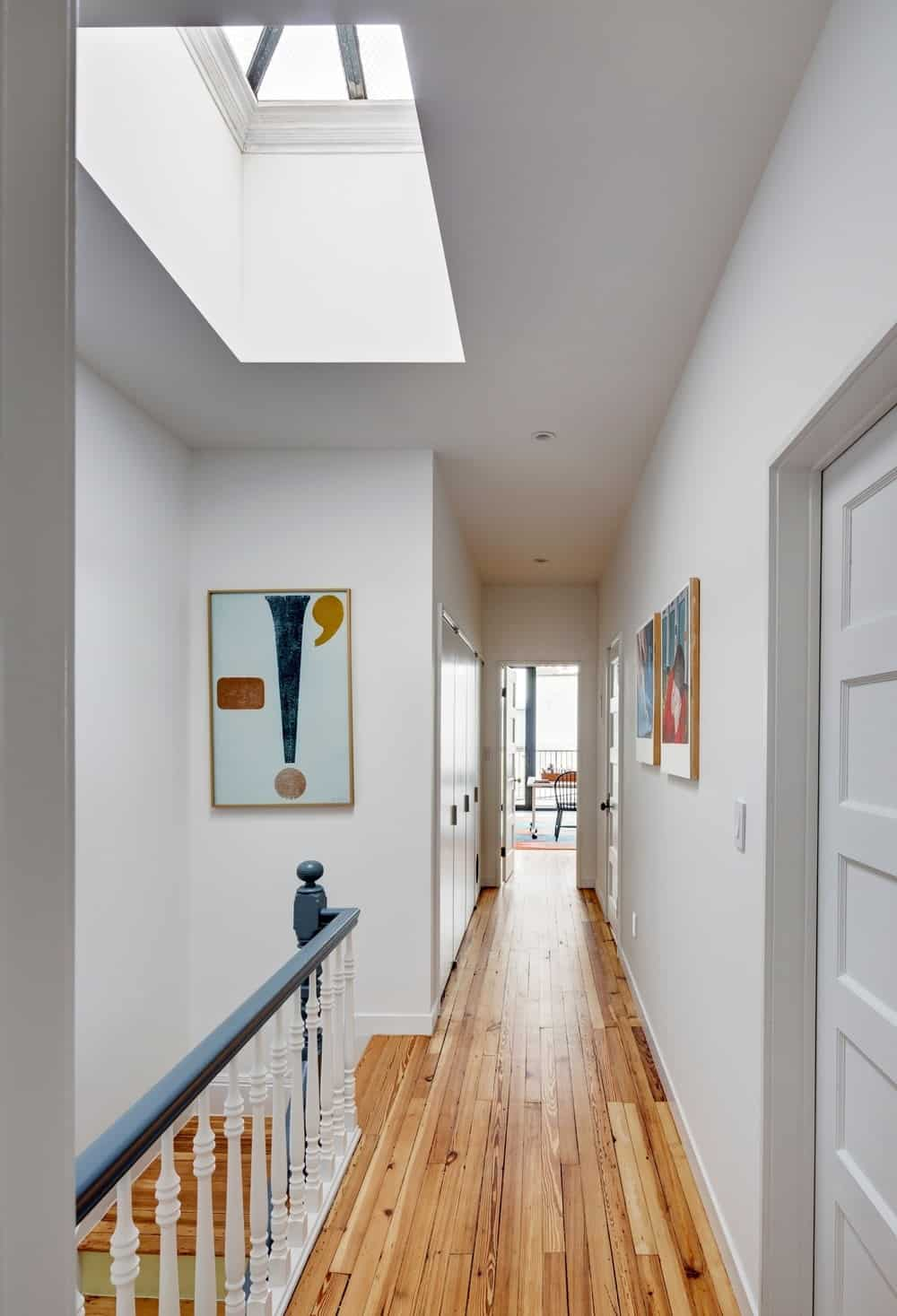 The hallway is lighted by the skylight adding brightness to the hardwood flooring and white walls. Photo Credit: Francis Dzikowski/OTTO