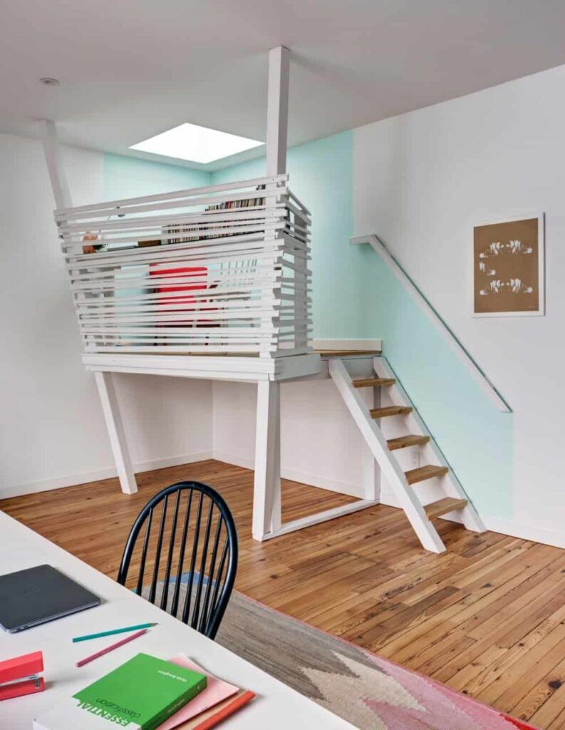 Small two-story home office showcases an open riser staircase leading to the elevated level enclosed with white wooden fence and lighted by a skylight.