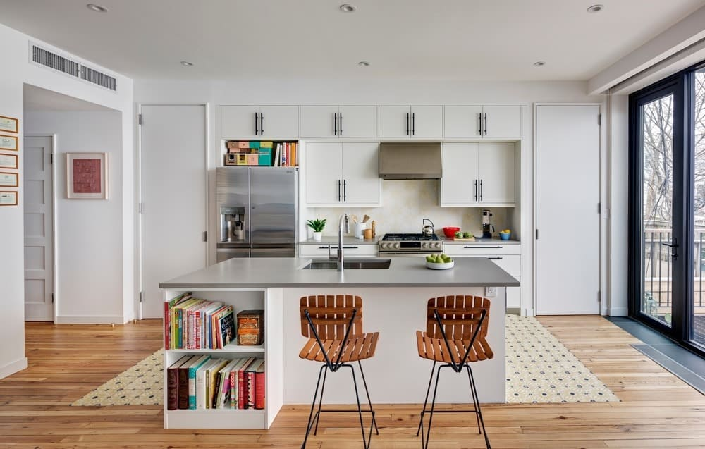 Perfect kitchen for book lovers. It features white cabinets with built-in bookshelves, stainless steel range hood, a huge patterned rug and a white breakfast island with gray countertop where a pair of wooden chairs sit.