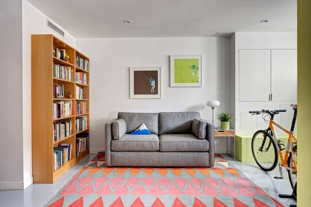 Another reading room providing peaceful space for reading books features a nice rug and gray sofa with tiles flooring. Photo Credit: Francis Dzikowski/OTTO