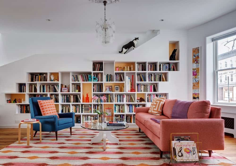Another living room with a wide bookshelf features a stylish rug on a hardwood flooring along with nice sofa set. A personalised cat lounge area can be sits on top of the shelf. Photo Credit: Francis Dzikowski/OTTO