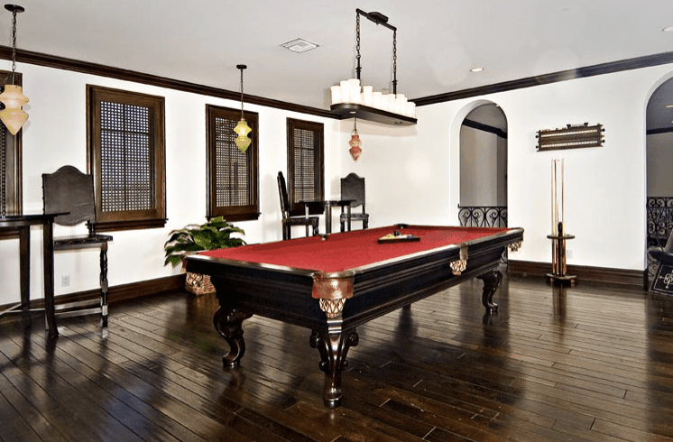 This Mediterranean home features white walls and hardwood flooring, along with a billiards pool set in the home's living room.