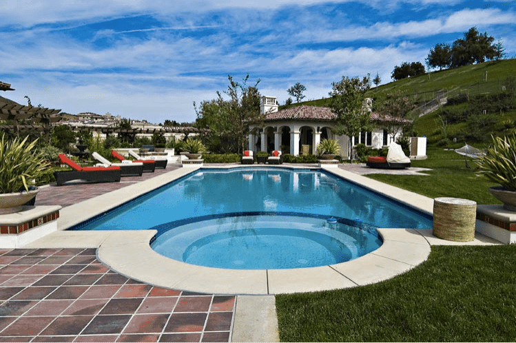 The Calabasas' bright skies is mirrored by the huge pool of the mansion.