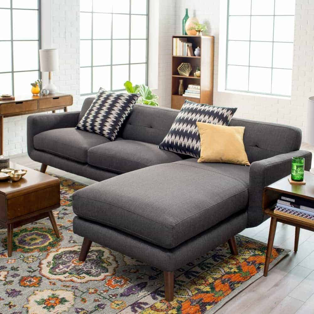 2 piece sectional sofa with 2 accent pillows and maple brown leg finish.