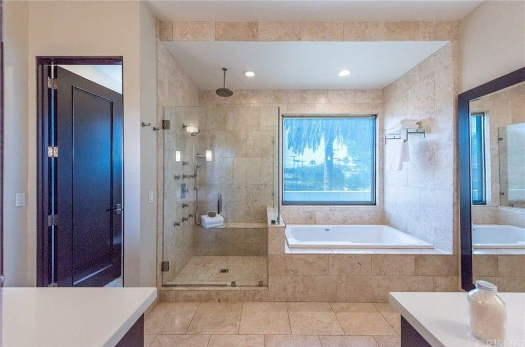 This master bathroom offers a corner shower area and a bathtub near the window. The beige tiles flooring matches well with the tiles walls.