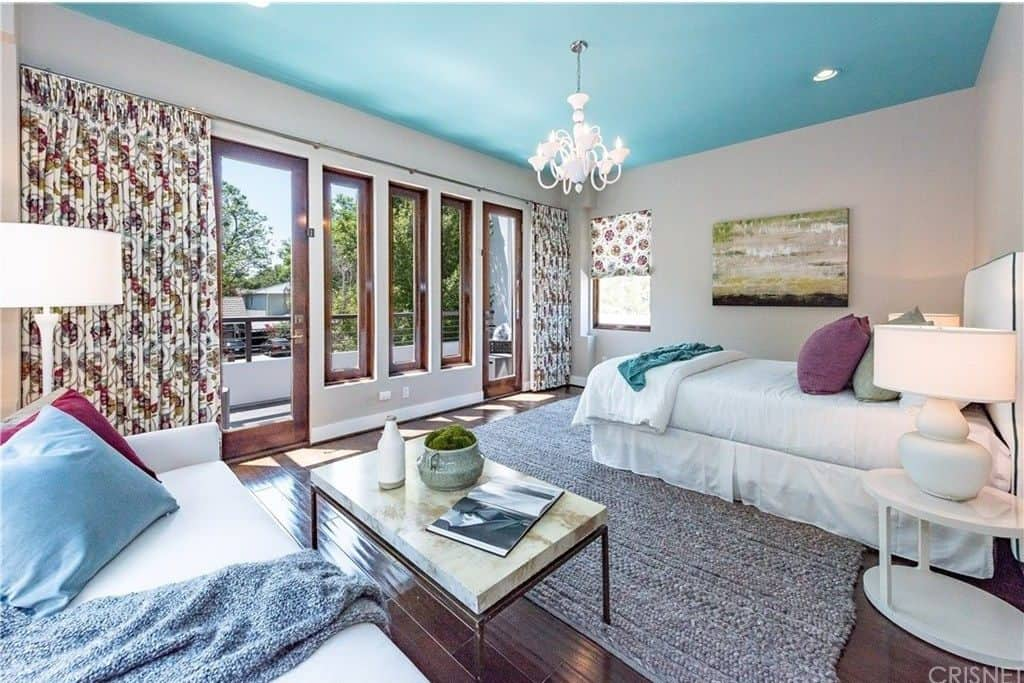 This primary bedroom offers a seating area with white sofa accented with multi-colored pillows and paired with a marble top coffee table. It has a sky blue ceiling with a hanging chandelier and glass doors that open to the balcony.