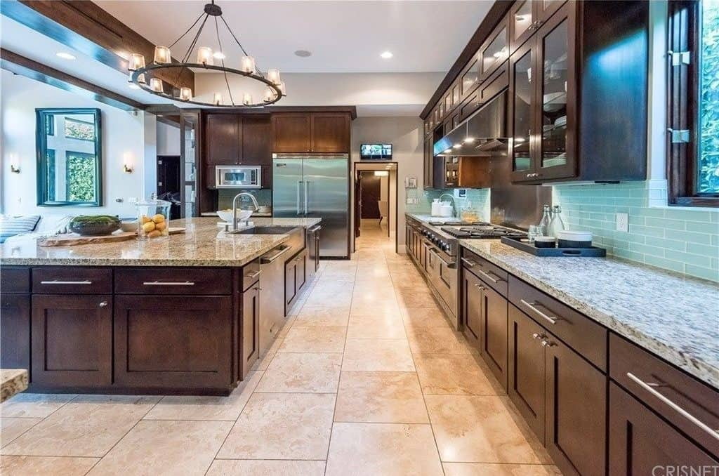 This kitchen features a long counter and a large center island, both boasting marble countertops.