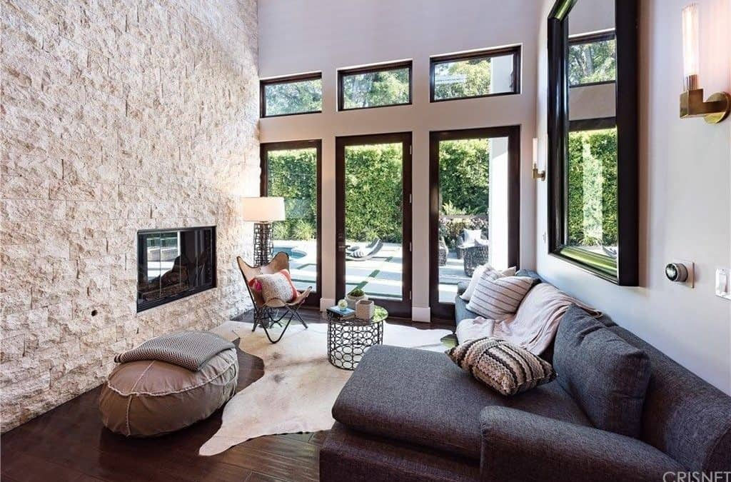 A small yet stylish formal living room with a jaw-dropping high wall with a fireplace. The sofa set looks perfect together with the hardwood flooring.