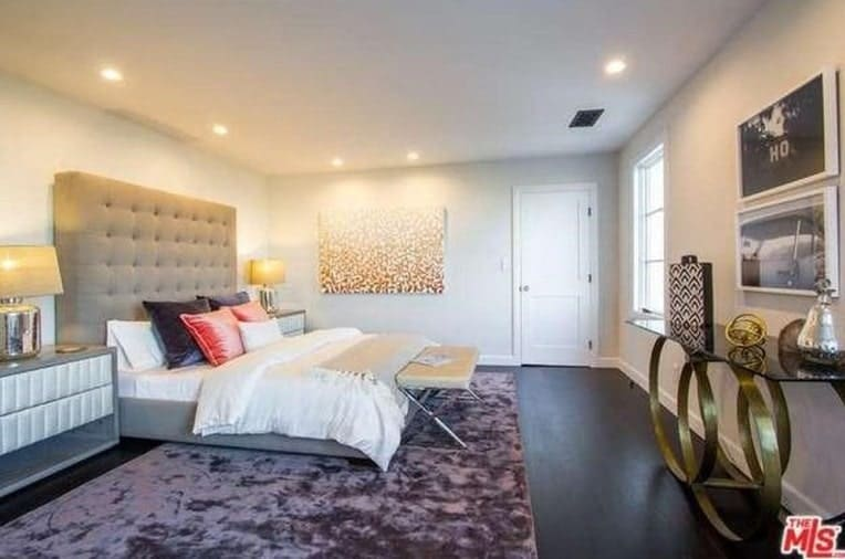 A spacious master bedroom with a luxurious bed, a stylish purple rug and white walls, lighted by recessed ceiling lights.