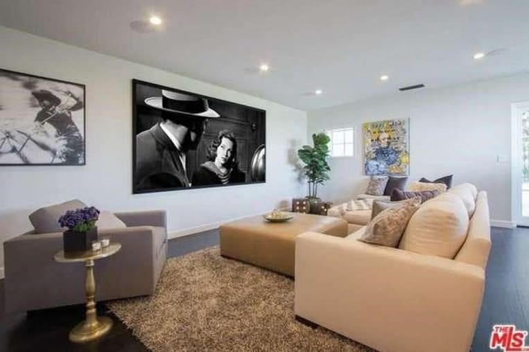 This large living room boasts a nice set of sofa in front of a theatre-like screen on the wall. This room is lighted by recessed ceiling lights.