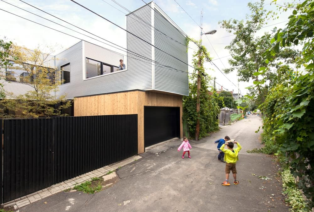 The outdoor view of the house featuring the property's black iron fence. Photo Credit: Maxime Brouillet
