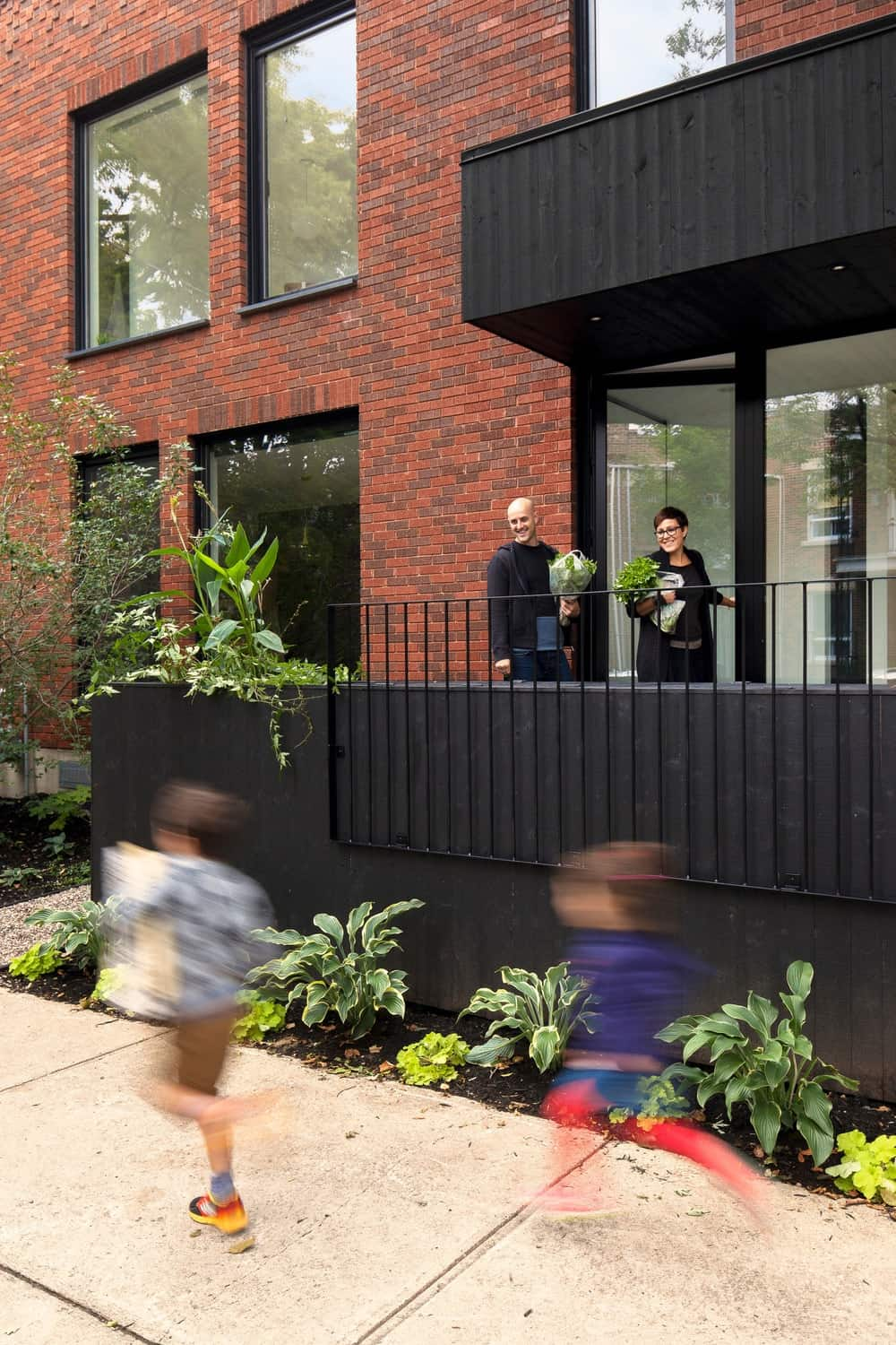 This outdoor view of the house shows the balcony coated by stylish black color. Photo Credit: Maxime Brouillet