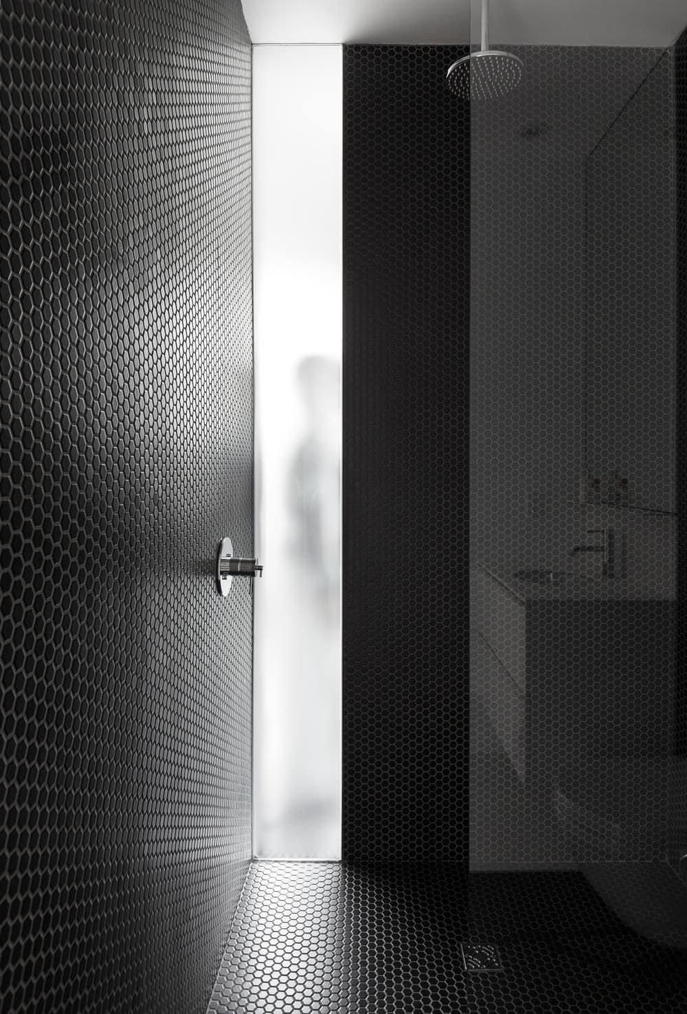 A contemporary black-themed walk-in shower also boasts its beauty in the house. Photo Credit: Maxime Brouillet