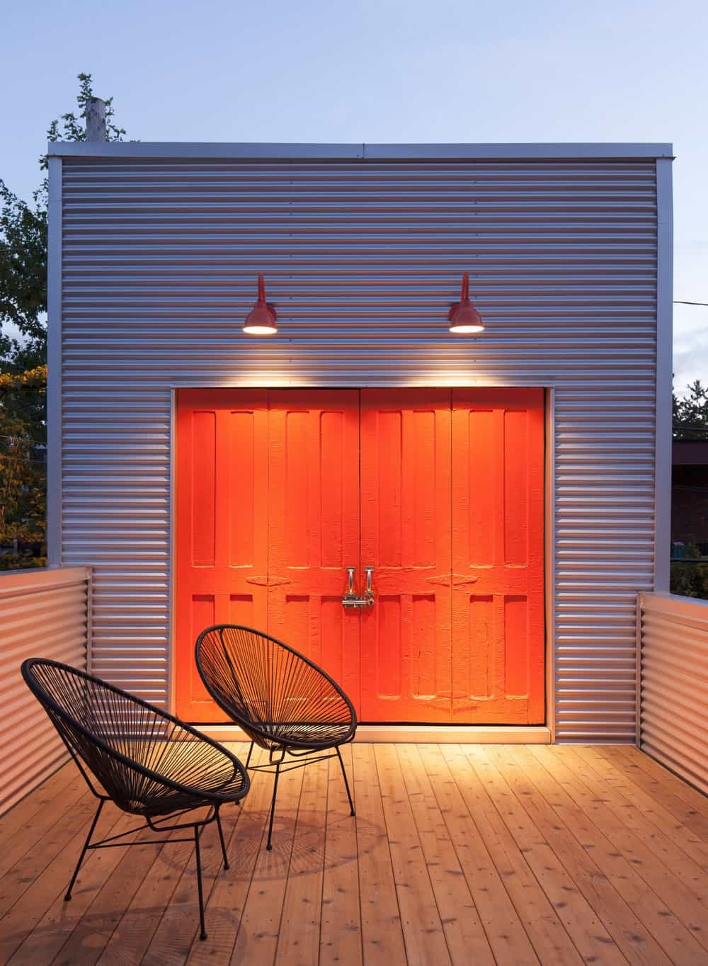 A terrace overlooks the area features a hardwood flooring and is lighted by a pair of wall lights and has a contemporary orange doors. Photo Credit: Maxime Brouillet