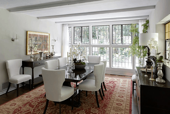 The dining room boasts an elegant theme featuring multiple glass windows blending with the white walls and dark hardwood flooring.