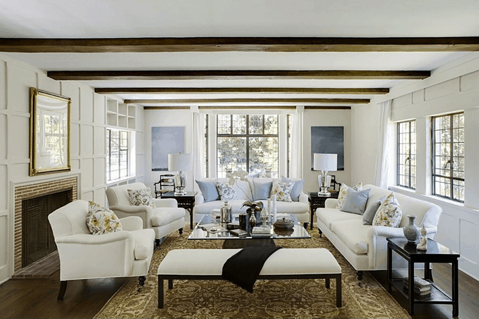 White formal living room featuring a ceiling with beams matching the hardwood flooring.