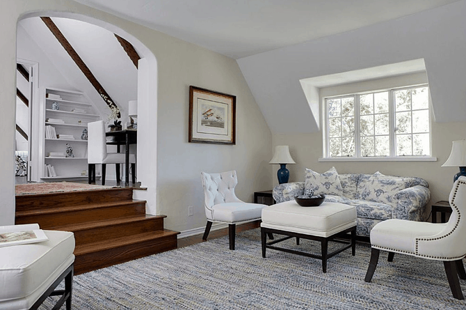 This foyer features a classy rug surrounded by white walls and ceiling.