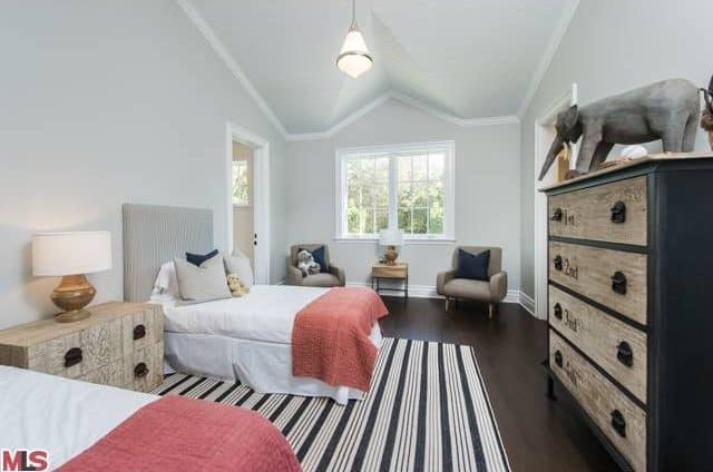 The bedroom features white walls and hardwood flooring. Cove ceiling has a pendant light.