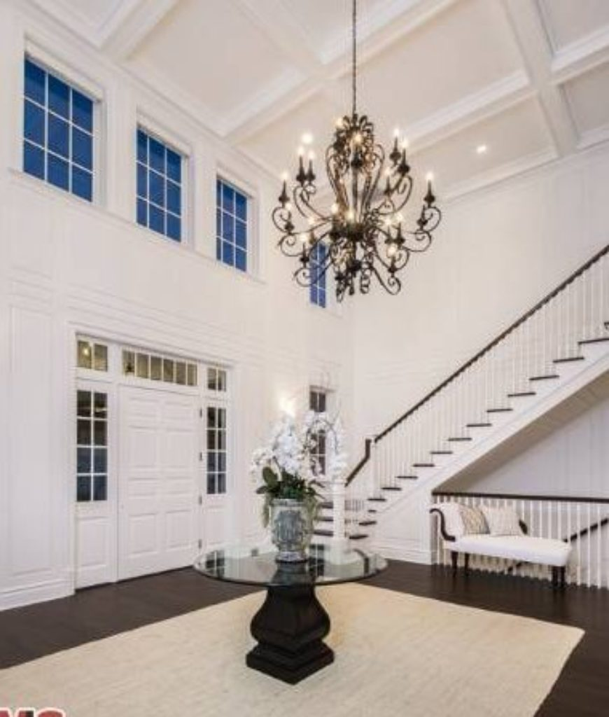 The grand foyer matched by a grand chandelier welcomes family and guests elegantly.