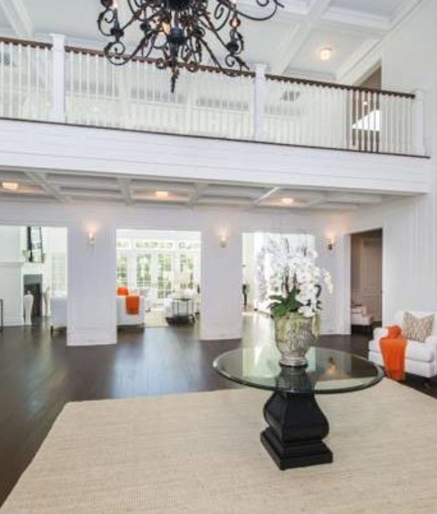 White walls cover the entire foyer while recessed lights and chandelier illuminates the area. Hardwood flooring is topped by a traditional rug.