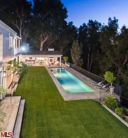 Aerial view showcases the well-maintained lawns and lounge area near the pool.