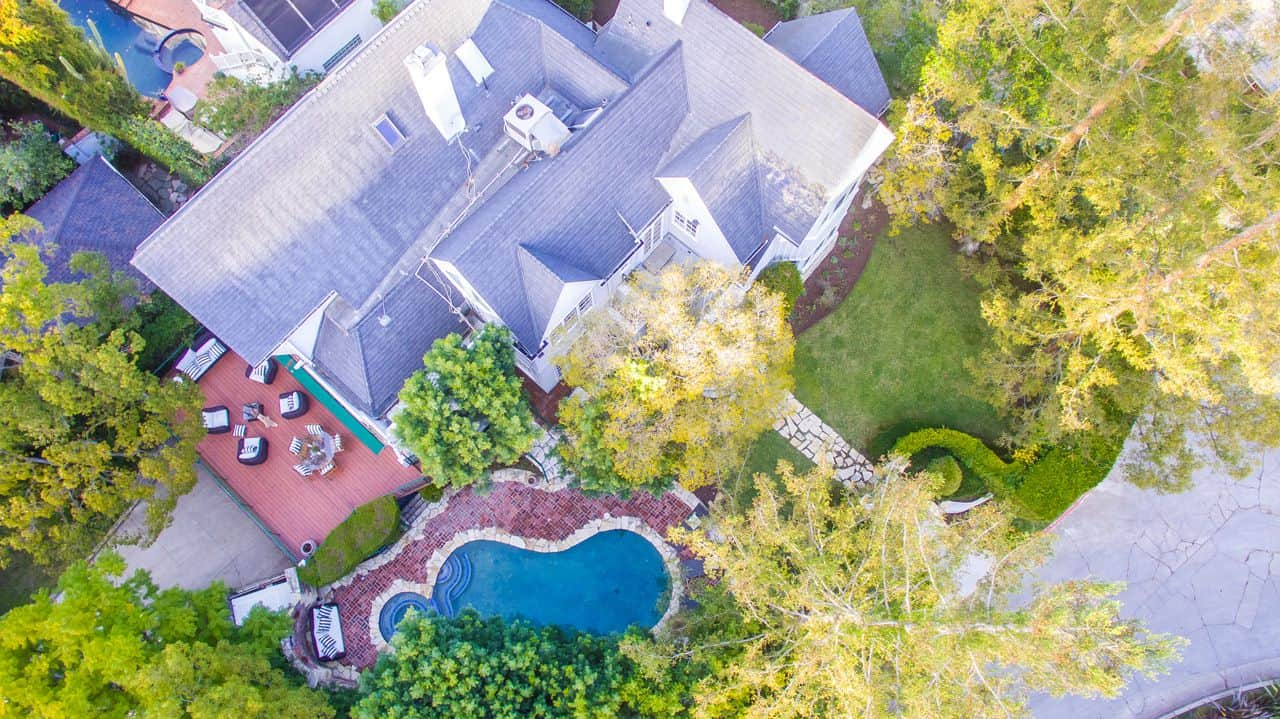 The aerial view of the house showcases the beauty of the place surrounded by healthy plants and trees.
