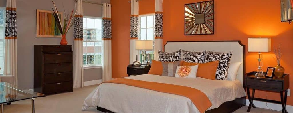 Bedroom with orange accent wall, pillows and vase with grey, beige and brown.