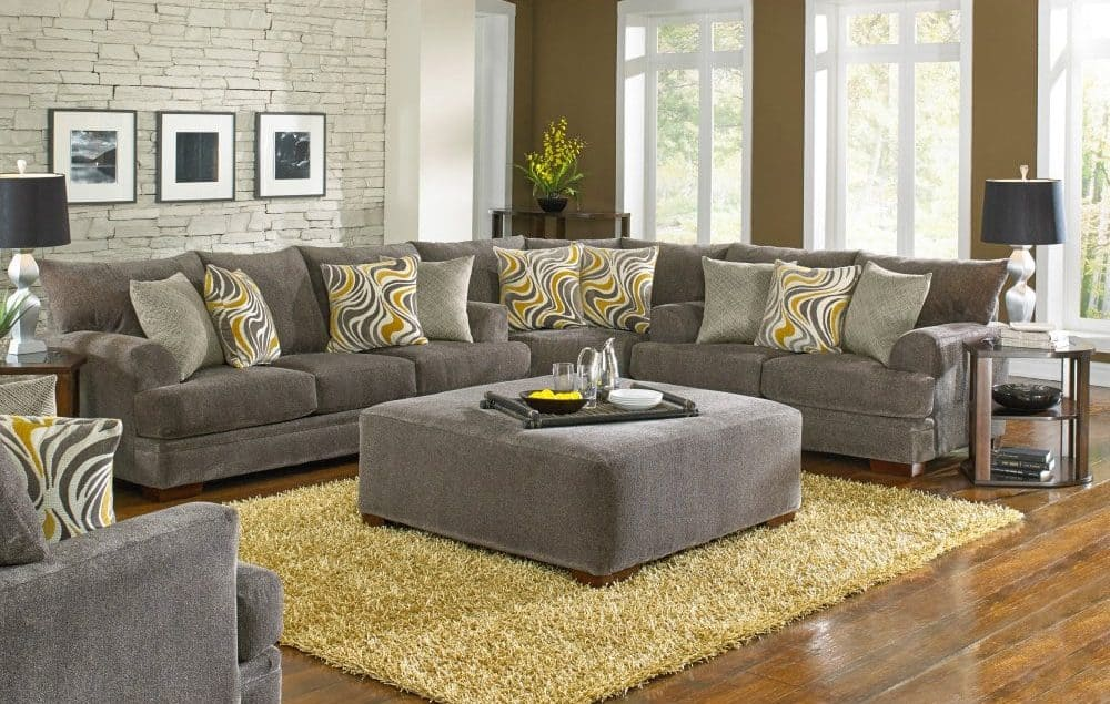 Crompton pewter sectional sofa with ottoman and shark fin arm design.