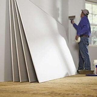 Man drywalling a wall inside a house