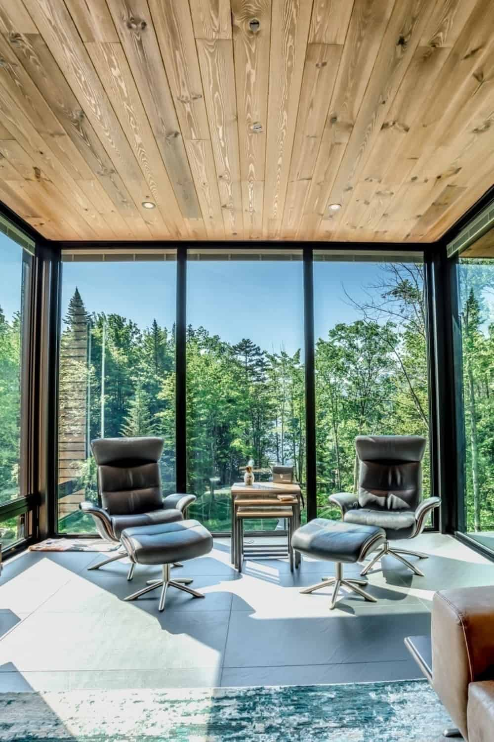 The living room also features a seating lounge near the tall glass windows great for viewing the beautiful outside landscape. Photo Credit: Dominic Boudreau