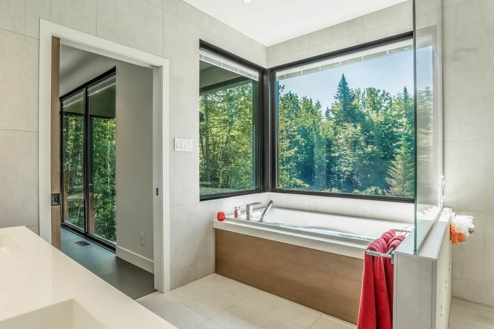 The soaking tub is placed at the corner near the clear glass window overlooking the outdoor landscape. Photo Credit: Dominic Boudreau