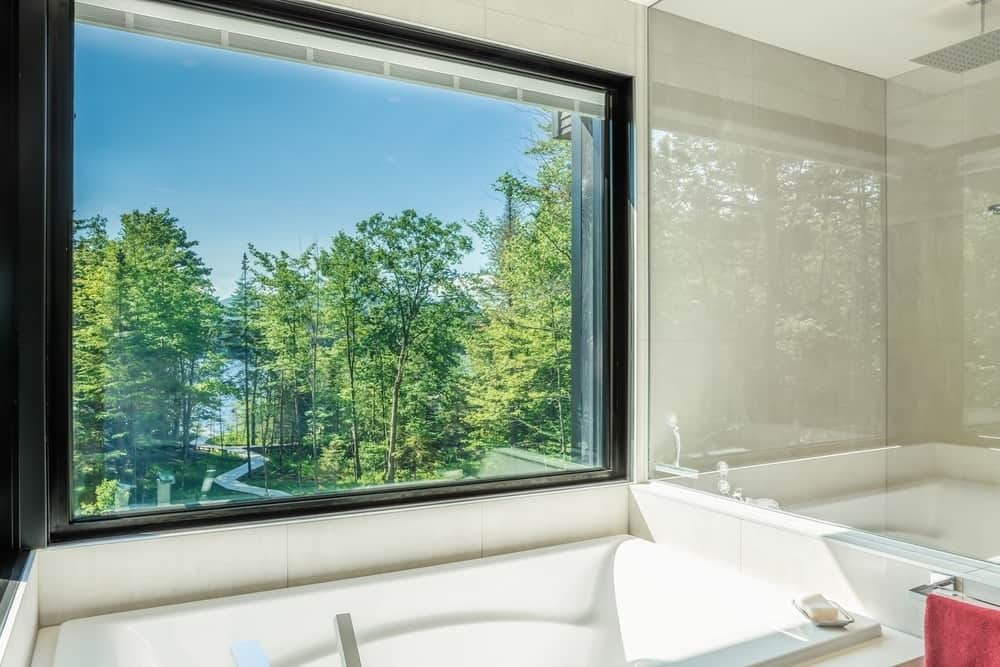 Another view of the bathroom showcasing the clear glass wall overlooking the outdoor landscape. Photo Credit: Dominic Boudreau