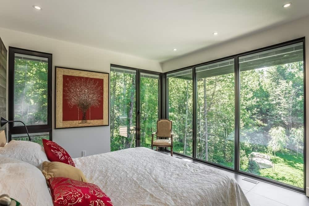 This primary bedroom is surrounded by glass windows overlooking the stunning outdoor views.