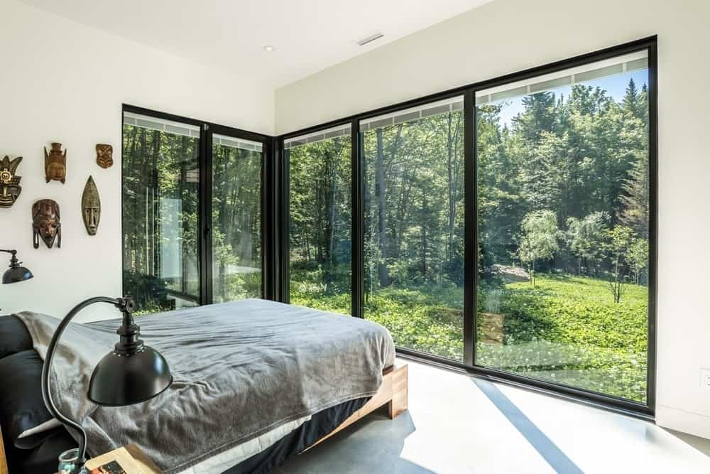 The bedroom is surrounded by glass windows offering amazing view of the outdoor landscape. Photo Credit: Dominic Boudreau