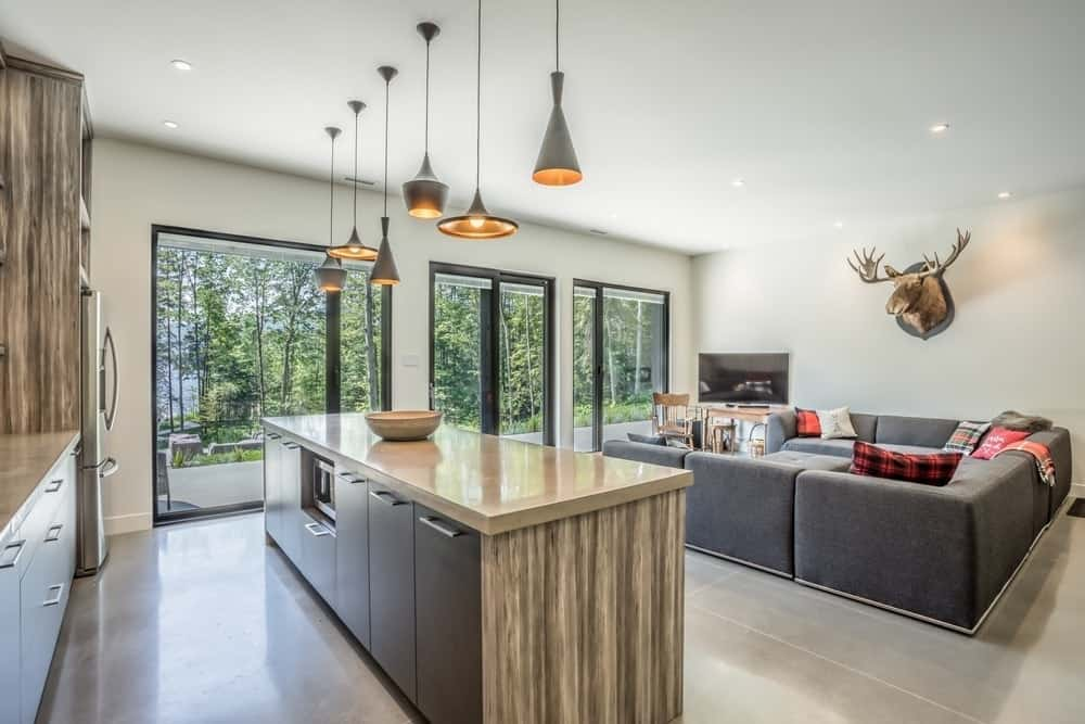 A modish kitchen setup featuring white walls and glass doors and windows overlooking the outdoor space. The narrow center island is lighted by a set of stylish pendant lights.
